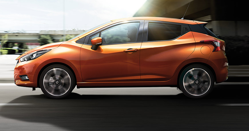 A new Nissan Micra in Energy Orange zips by a motorcycle