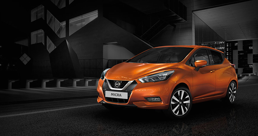 A rear and side view of an energy Orange new Nissan Micra